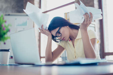 Jonge mooie zakenvrouw is casual kleding en glazen is moe van het werk in het kantoor, crumpling papers Stockfoto