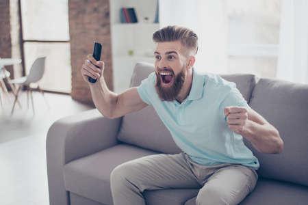 골! 젊은 수염 된 남자 흥분된 footbal 집에서보고있다, 그는 그의 손에 콘솔 잡고 그의 자신의 좋아하는 팀의 승리를 축하