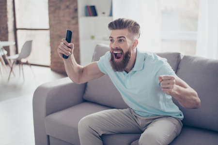 Goal! Young excited bearded man is watching footbal at home, he is holding console at his hand and celebrating the victory of his favourite team Stock Photo