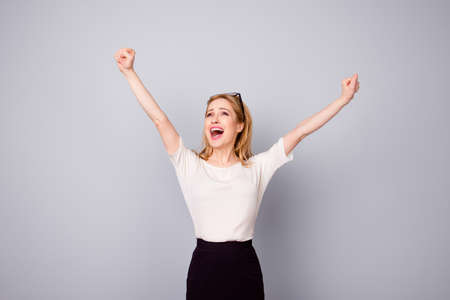 Yes! Pretty extremely happy woman celebrating her success with raised hands
