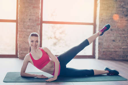 Attractive young lady is doing stretching before start her training, to be bendy and flexible. She is wearing modern sportswear