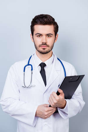Vertical photo of serious confident bearded doctor with stethoscope and clipboard ready for the consultation
