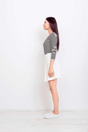 カジュアルな服と白い靴のブルネットの少女の純粋な白い背景の上のフルサイズ縦断ビュー