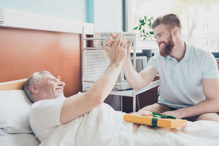 Give me five! Young stylish red bearded guy is visiting and cheering up his grandpa lying in bed at the modern hospital ward Stock Photo