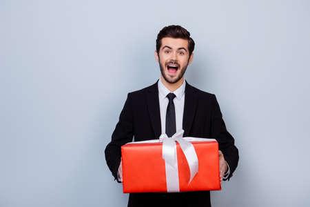 Excitado e impresionado hombre en traje negro celebración de gran caja de regalo de color rojo sobre fondo gris Foto de archivo - 81816546