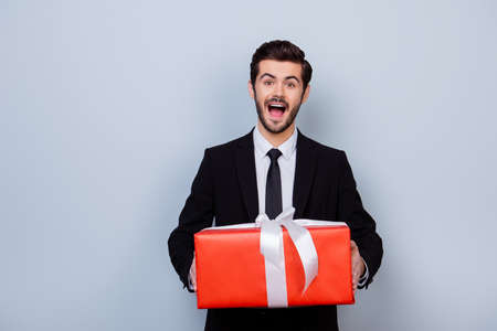 Excited and impressed man in black suit holding big red gift box on gray background 版權商用圖片