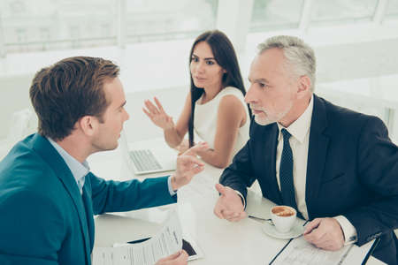 Business partners are discussing the  financial growth of their company. Young one is existing on his ideas, old one is focused and listening Stock Photo