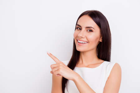Successful smiling businesslady is pointing away with finger. She is in isolated on the pure white background