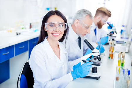Success in inventing new technology! Young lab worker is smiling and her colleagues are working for experiment. They have all modern equipment they need Stock Photo