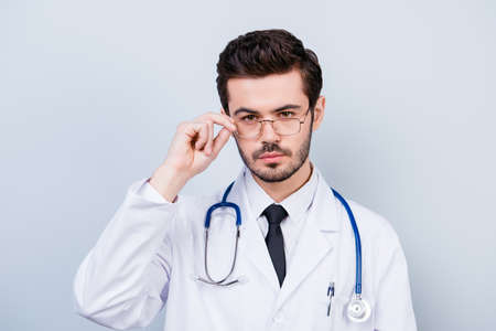Portrait of serious confident young doctor touching his glasses