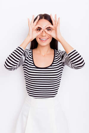 Close up portrait of cute playful girl. She is wearing casual clothes and stands on pure white background, amazed, gesturing fingers like glasses Stock Photo