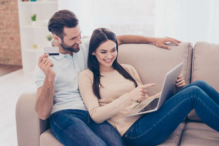 Cheerful man and woman are making internet shopping with laptop and bank card at home in cozy living room Stock Photo