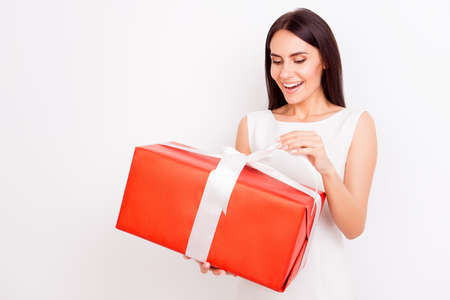 Happy amazed gorgeous brunette is holding big red present box on white background. She is smiling, dressed in white outfit on pure background