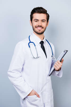 Vertical portrait of successful happy smiling doctor in uniform holding clipboard Stock Photo