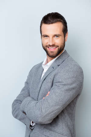 Vertical photo of smiling cheerful entrepreneur standing with crossed hands on gray background