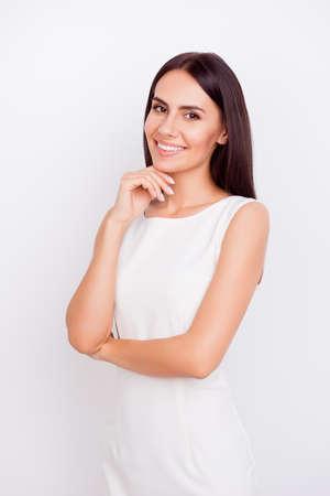 Portrait d'une fille mignonne mince en tenue stricte blanche. Elle a du succès et est belle. Derrière est un pur fond