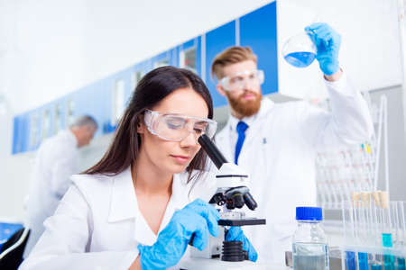 Team work. Young lab worker in safety glasses is analysing the sample in the microscope. She is in a labcoat, in the middle of experiment Stock Photo