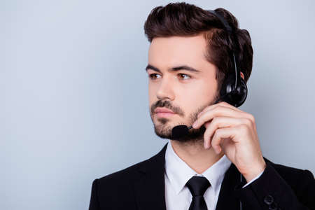 caller: Close up portrait of concentrated man in formalwear trying to adjust the microphone of his headphones
