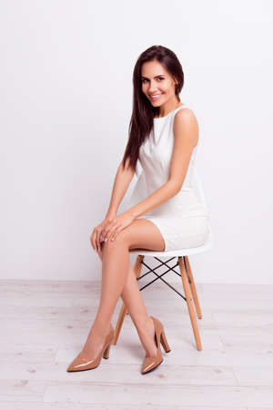 Full size portrait of successful gorgeous lady. She is wearing formal white stylish dress and high hills shoes, sitting on a chair on pure background