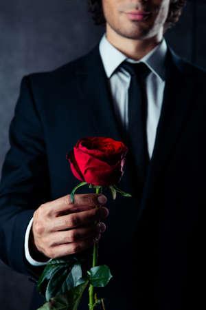 彼の手に赤い薔薇を持ってビジネスの男性の写真をトリミングしました。彼はフォーマルな服装を着ています。