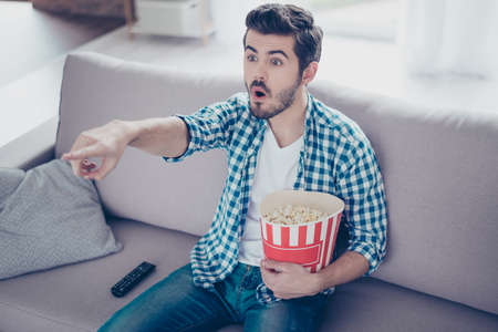 watching horror: Portrait of impressed man in checkered shirt eating popcorn while watching films on tv at home and having fun