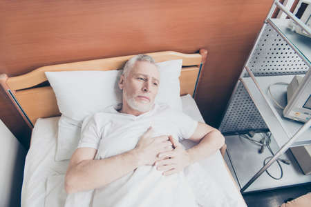 Aged patient is lying in the bed and holding his hands near to heart. He feels lonely and sad, he dreams to be healthy Stok Fotoğraf