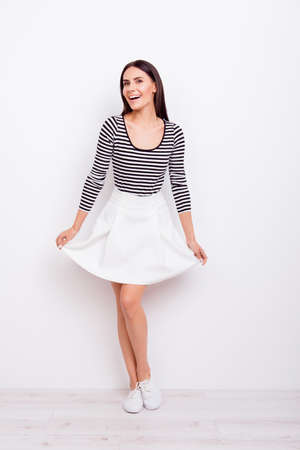 Full length portrait of gorgeous playful lady. She is wearing casual outfit and stands on pure white background holding her skirt Stock Photo