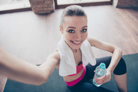 Close up portrait of excited girl in gym. She is making selfie with camera on her smartphone, smiling and holding bottle of water Stock Photo