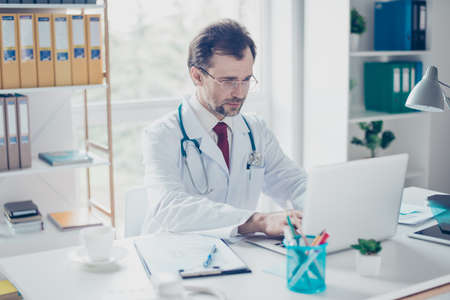 experiencing: Serious doctor is browsing info on hia computer. He is in a white coat, glasses, sitting in modern office
