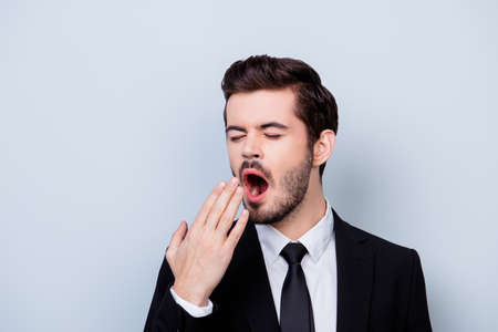 Close up portrait of bored in formal clothes yawning man isolated on gray background Zdjęcie Seryjne
