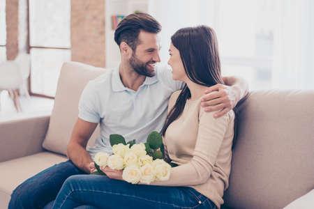 幸せな一緒に。男は手にバラで彼のガール フレンドを包含しています。彼らは自宅のソファの上が
