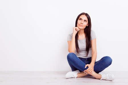 Portret van aantrekkelijke dromerige nadenkende brunette dame. Ze draagt casual outfit en zit op de vloer met gekruiste benen op pure witte achtergrond