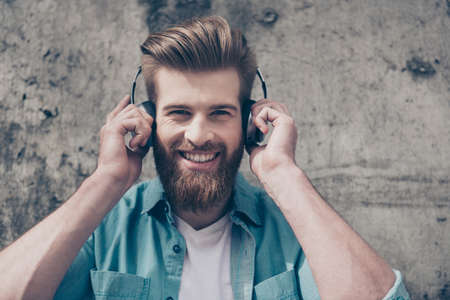 Handsome stylish red bearded guy with beaming smile and perfect fashionable hairdo is listening to music outside with big headphones