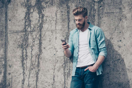 Pensive brutal young red bearded guy is typing a message outdoors. He is very stylish, wearing jeans casual clothes Banco de Imagens - 82093316
