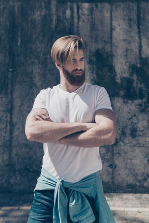 Young hot bearded guy in casual clothes outdoors. His hairdo is so stylish and his arms are so muscular