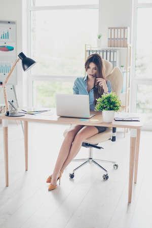 Foto van de volledige grootte van elegante zakelijke dame zitten in haar kantoor en bladeren info in de laptop. Ze draagt ??formele kleding en hoge heuvels