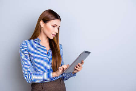 Young attractive business lady is holding tablet and typing on it. She is wearing smart formal clothes and behind her is a pure background Stock Photo