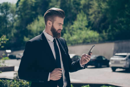 Young stylish bearded business man in a classy suit is browsing his pda on the street at the sunny day. He is ordering a cab by pda