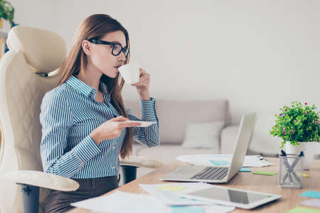 Successful relaxed economist is resting at her work place and drinks coffee while reading her mail on the laptop Stock Photo