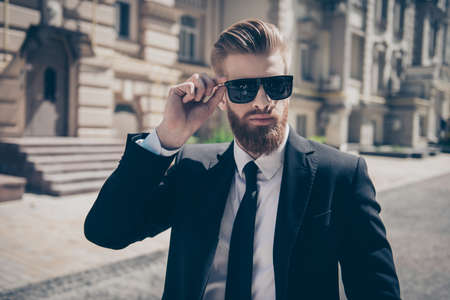 Close up of a famous guy in formal wear and sunglasses outdoors. He has very stylish bear and hairdo Stock Photo