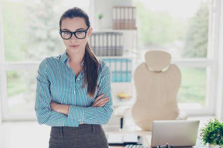 成功のコンセプトです。眼鏡とポニーテール、厳格な服装の彼女のオフィスに立って真面目若い女性の肖像画 写真素材
