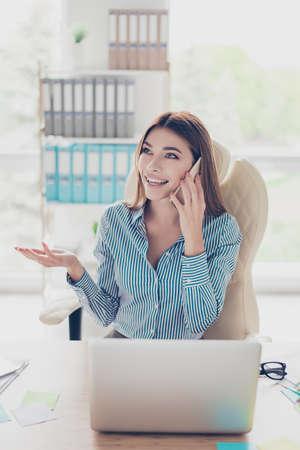 De glimlachende charmante jonge bedrijfsdame spreekt op de telefoon in bureau. Ze draagt ??formele kleding