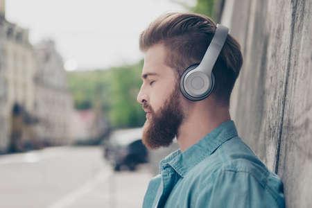 Wat een genot. De jonge aantrekkelijke rode gebaarde kerel luistert aan muziek op de straat. Hij is ontspannend en droomt