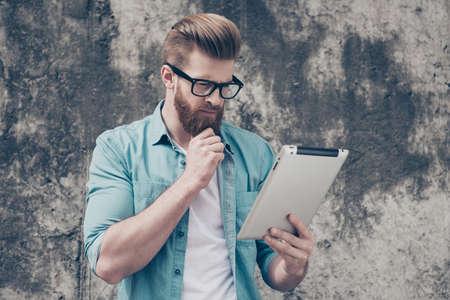 カジュアルな服装の若い物思いにふけるオタクひげを生やした男が屋外の情報を参照してください。非常にスタイリッシュで、深刻です 写真素材