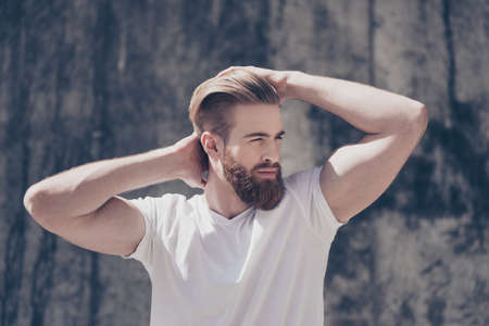 Stylish young red bearded guy in  casual clothes outdoors. He looks serious, fixing his perfect hairdo