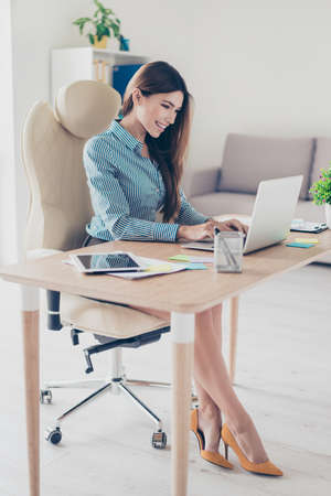 Full size photo of elegant business lady sitting in her office and typing in laptop. She is wearing formal wear and high hills