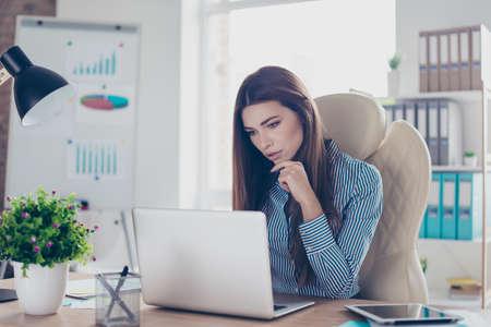 공식적인 착용에 심각한 젊은 사업가의 초상화, 그녀의 직장에 앉아 노트북의 데이터에 집중 스톡 콘텐츠
