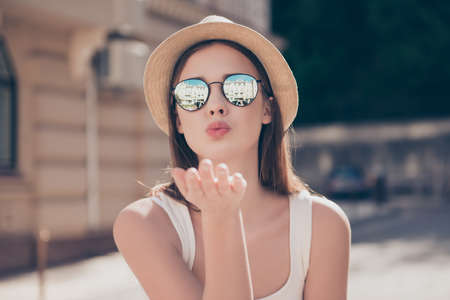 Kiss for you! Happy carefree girl on a holiday is sending an air kiss to her lover. She is in a fashionable hat and sunglasses Stock Photo