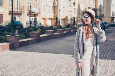 幸せな若い女の子でスタイリッシュな帽子とサングラス、休暇中に純粋な光のドレスとカーディガンを着て、帽子を押し、ポーズ