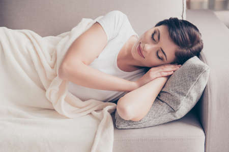 Close up of a young gorgeous brunette sleeping on the beige cozy sofa. Her head is on grey pillow and she is covered with light blanket